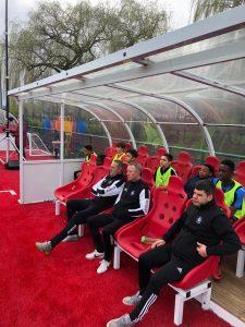 Elites coaches sitting in team dugout.